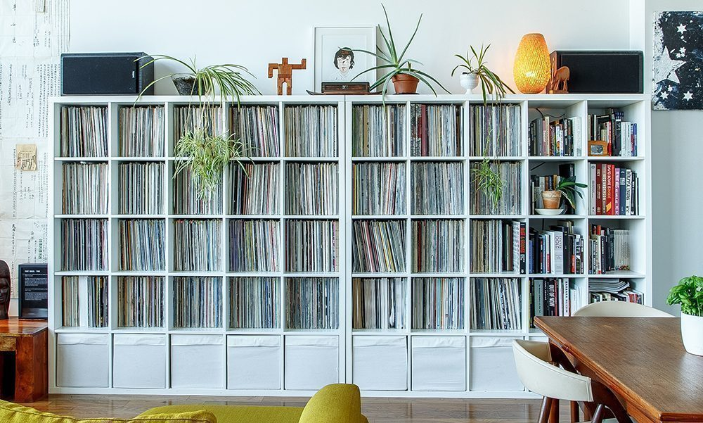 10 white bookcases in a row filled with books and records