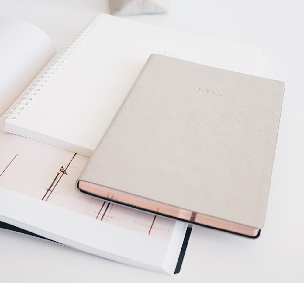Gold notebook on top of white notebook on top of a planner