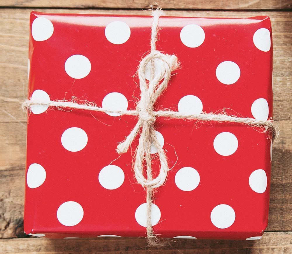 Square gift wrapped with red wrapping paper, white polka dots and brown string tied in a bow