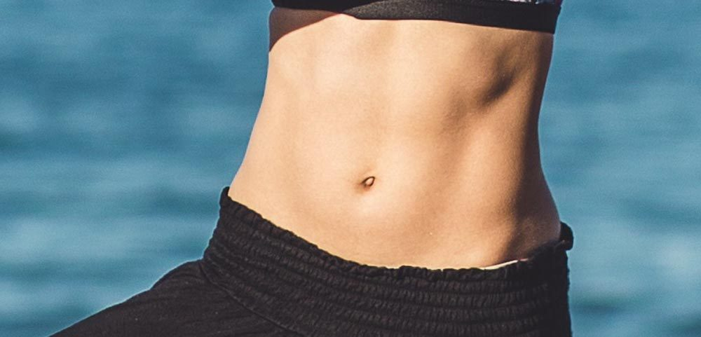 women wearing black yoga pants showing abs