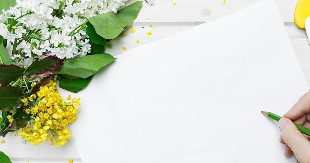 white sheet of paper with hand holding a green pencil. Yellow and White flowers around the top left corner