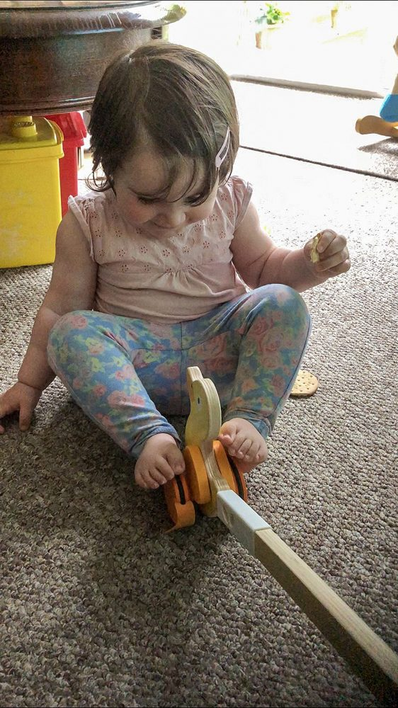 Lottie playing with the wooden yellow ducky