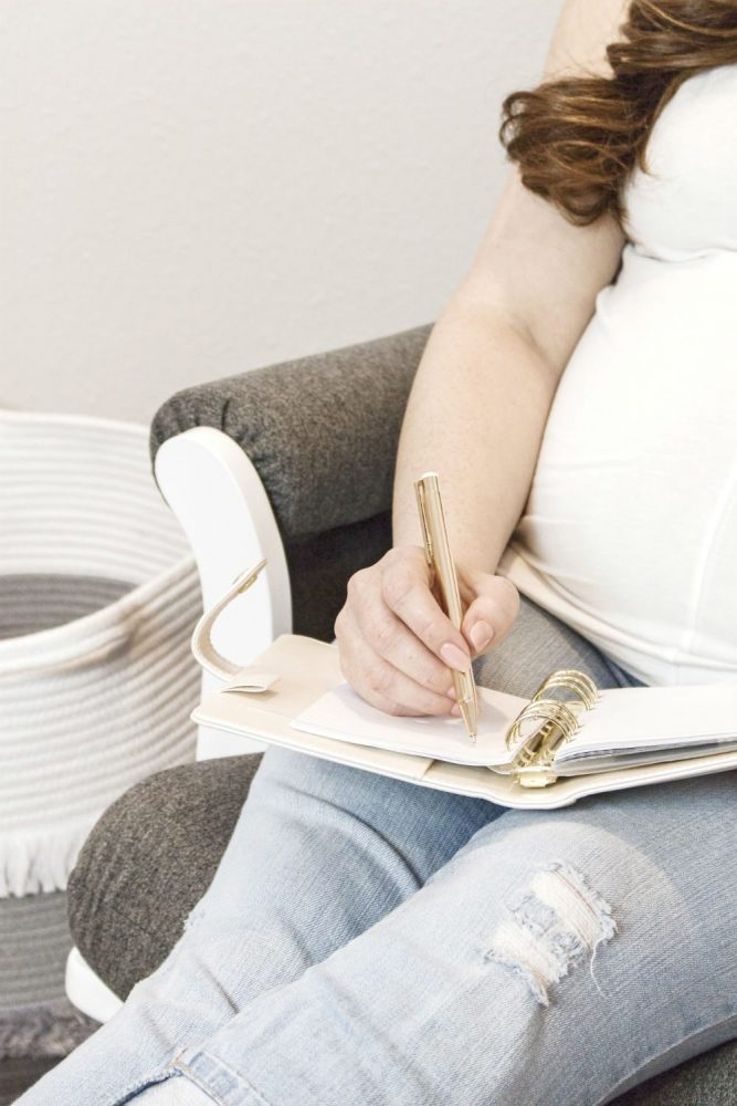 Pregnant women sat on a grey chair, writing in a note book