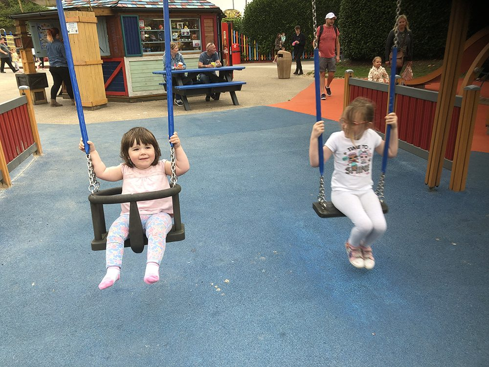 Lottie and Mia swinging on the swings