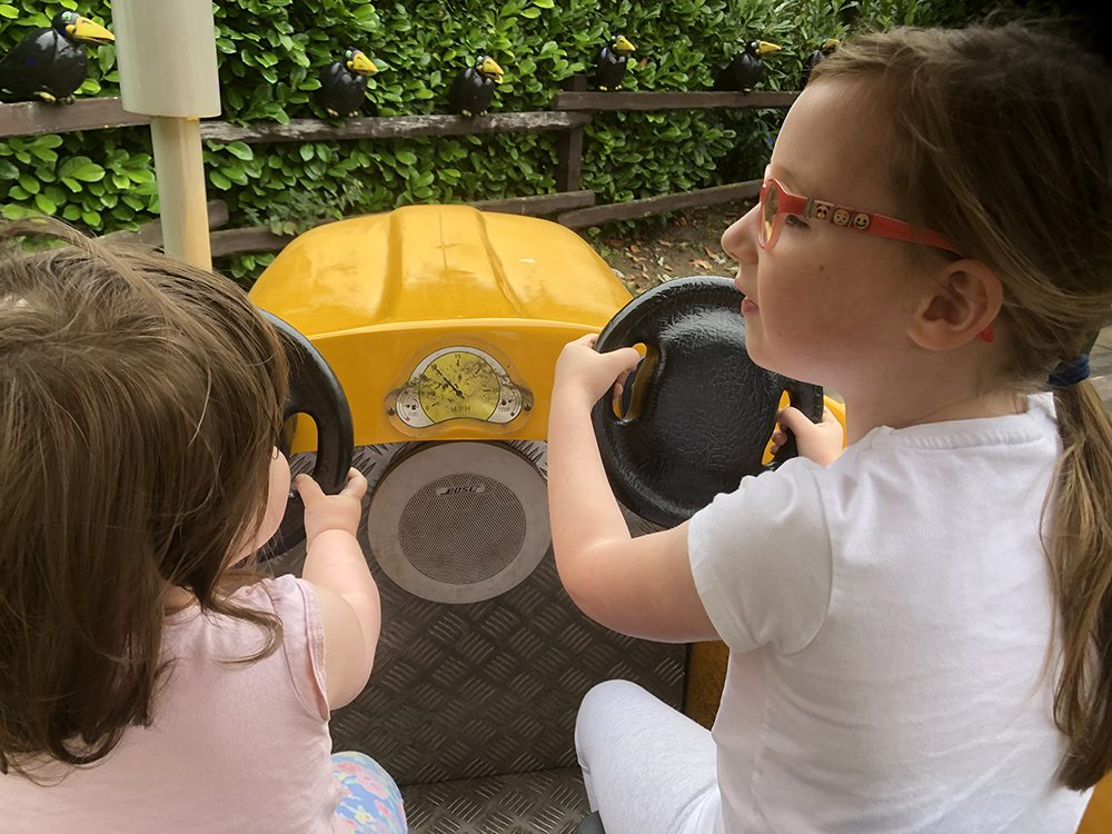 Mia and Lottie driving the little yellow tractor