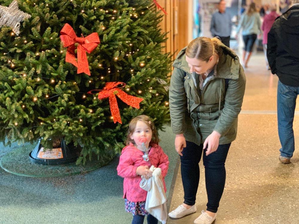 Lottie stood beside a Christmas tree