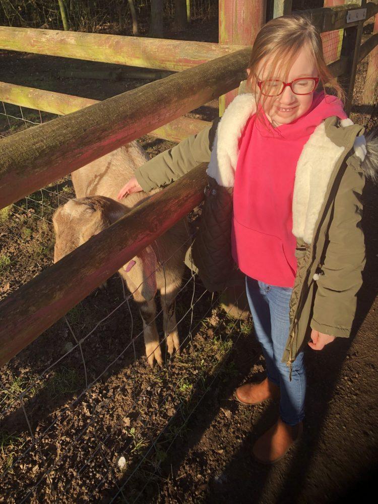 Mia stroking a goat