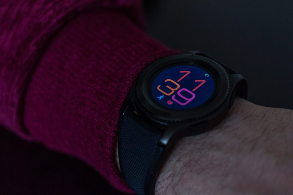 A round smartwatch on a mans arm showing the time in colourful numbers