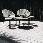 2 chairs and a wooden table places on circular outdoor decking