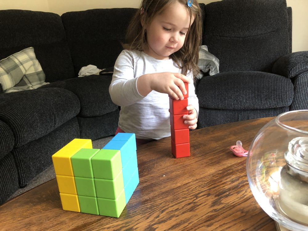 Lottie building a Geomag block tower