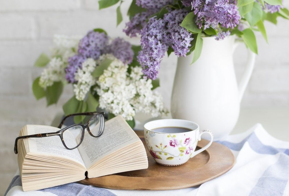 Coffee and open book next to vase with purple flowers in