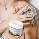 Women with tub of CBD cream