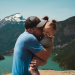 Man holding his daughter and kissing her