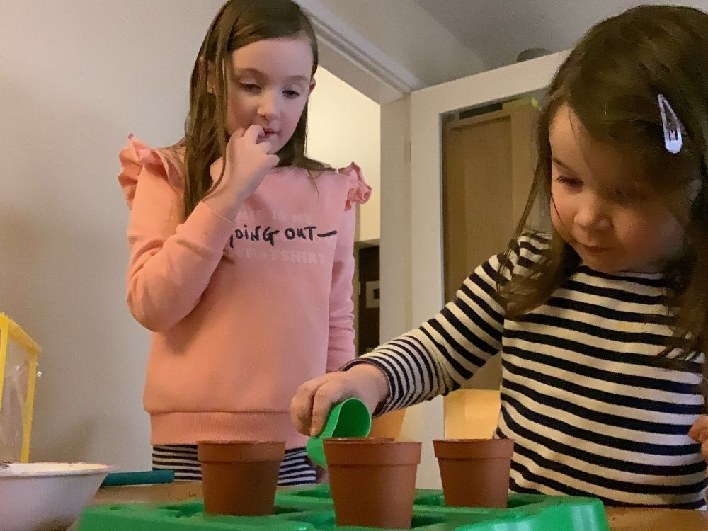 Lottie pouring water into the flowerpots with a small green container