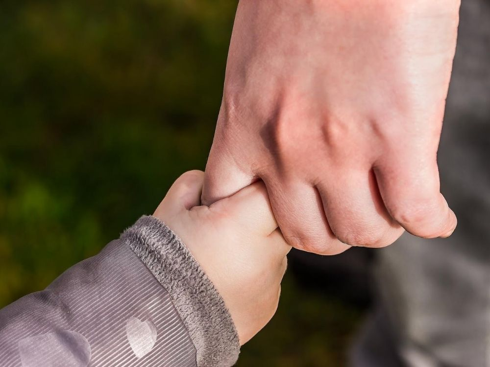 Childs hand holding an adults hand