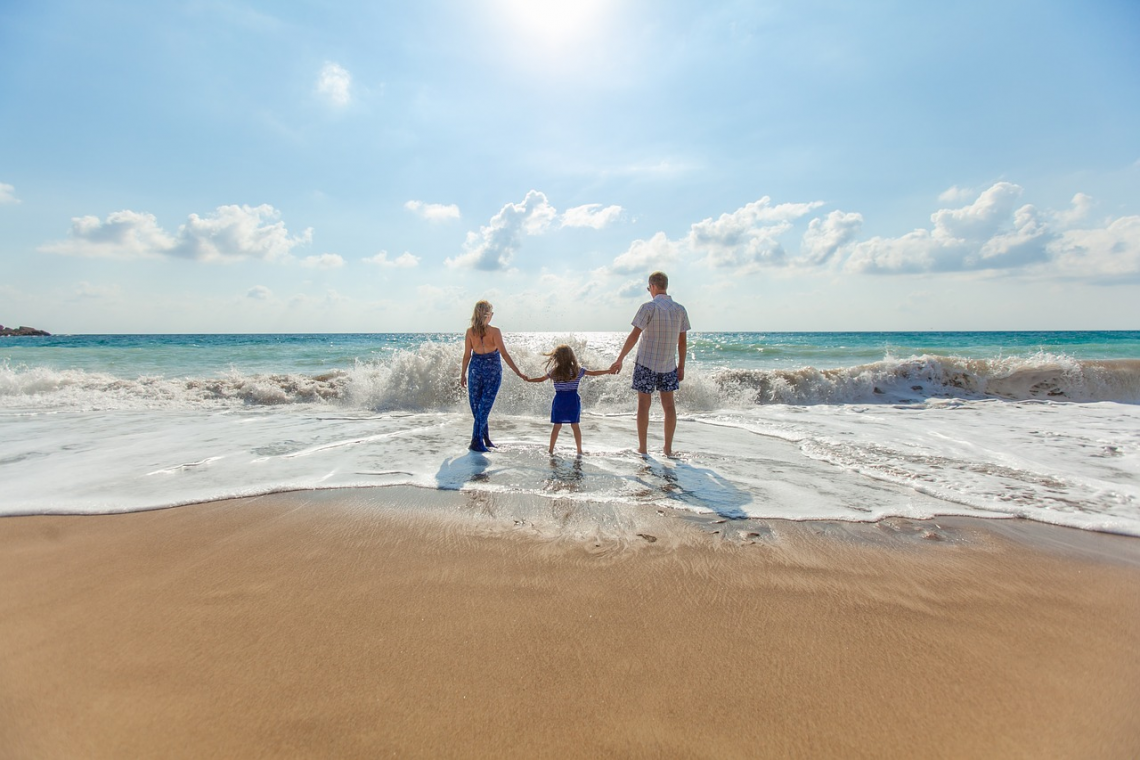 Photo of family holding hands on a beach