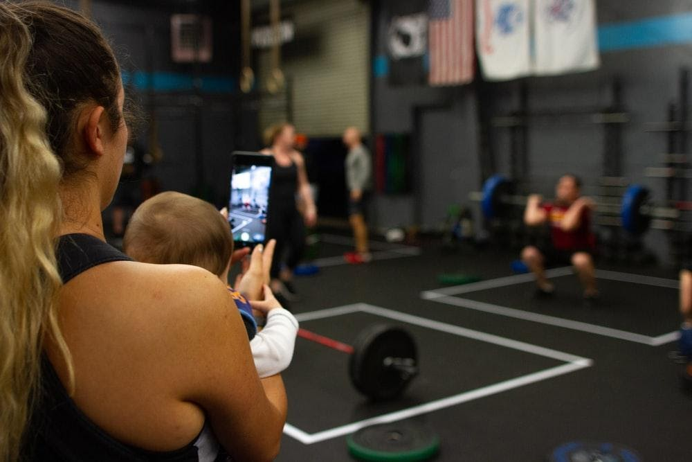 Mum holding baby while working out